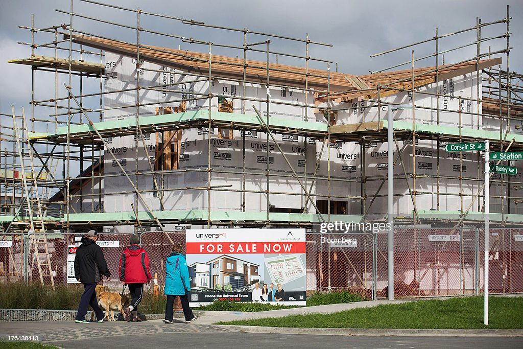 Pedestrians walk with a dog past a house under construction in the suburb of Hobsonville Point in Auckland, New Zealand, on Tuesday, Aug. 13, 2013. New Zealand's growth rate is forecast to outpace Australia's for the next two years, helping stem an exodus that's resulted in the highest proportion of its people living overseas in the developed world after Ireland. Photographer: Brendon O'Hagan/Bloomberg via Getty Images