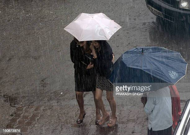A pedestrians walk with an umbrella as it rains in New Delhi on August 24 2012 Nationwide the monsoon has been more than 20 percent below its average...