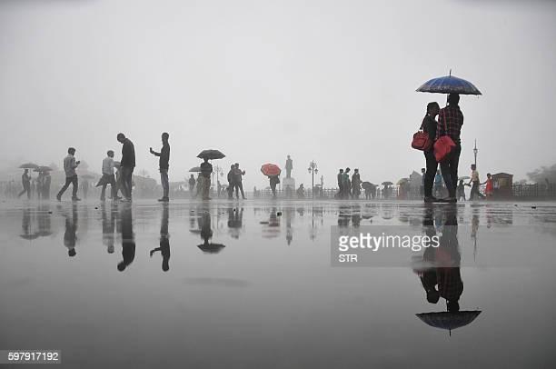 Pedestrians walk with umbrellas during rainfall in Shimla on August 30, 2016. / AFP / STR