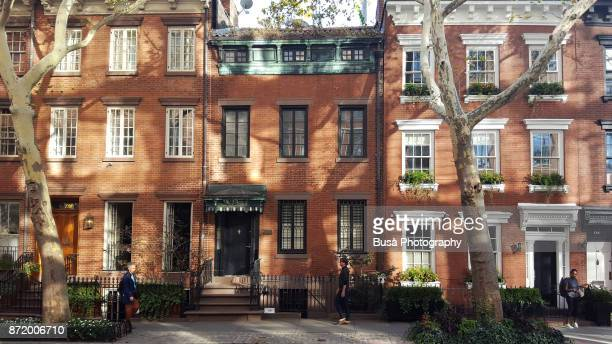 New York City, USA - September 29, 2017: Pedestrians walking along elegant brownstones and townhouses in the West Village. Manhattan, New York City