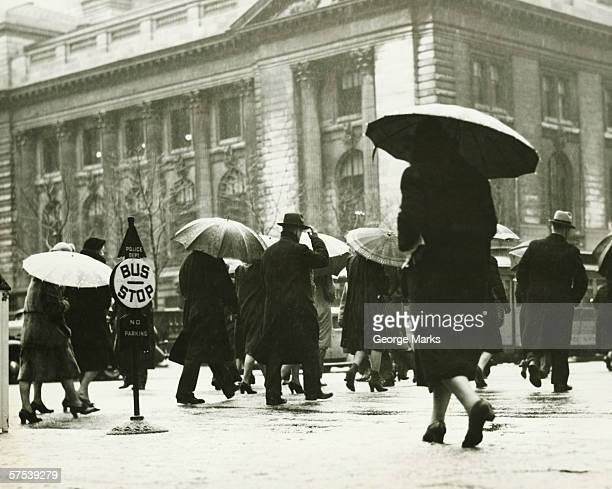 pedestrians walking in rain in new york city, (b&w) - history stock pictures, royalty-free photos & images