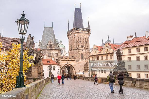 pedestrians walking on charles bridge towards the charles bridge tower, prague, czech republic - charles bridge stock photos and pictures