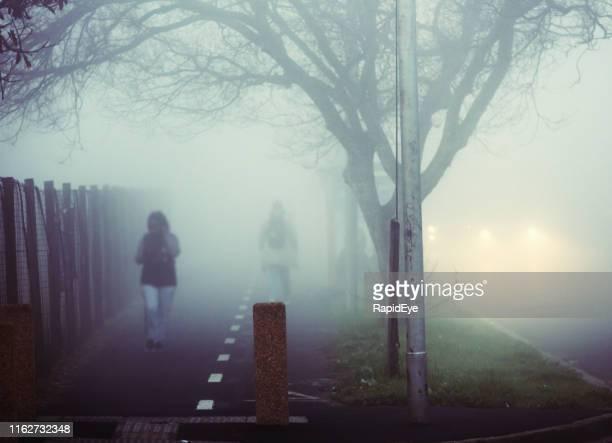 pedestrians walking on sidewalk in thick mist - nebbia foto e immagini stock