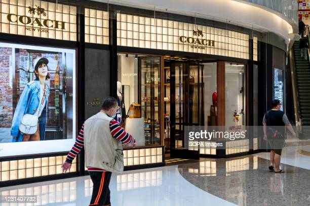 Pedestrians walking past an American multinational fashion and luxury accessories chain brand, Coach store and logo seen in Hong Kong.