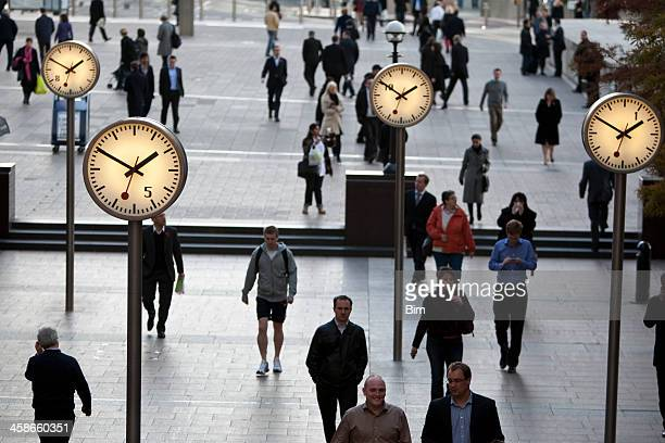 Pedestrians walking past clocks in Canary Wharf London's Financial District