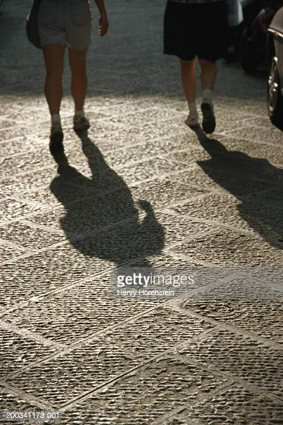 pedestrians walking, shadows falling on street, low section, rear view - henry street stock pictures, royalty-free photos & images