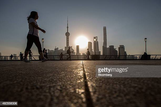 Pedestrians walks along the Bund while buildings of Pudong's Lujiazui financial district stand across the Huangpu River as the sun rises in Shanghai...
