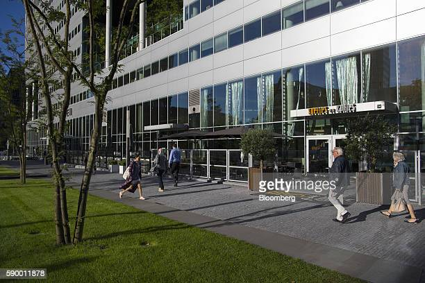 Pedestrians walks between a green outdoor space and commercial office buildings in the Zuidas business district of Amsterdam Netherlands on Monday...