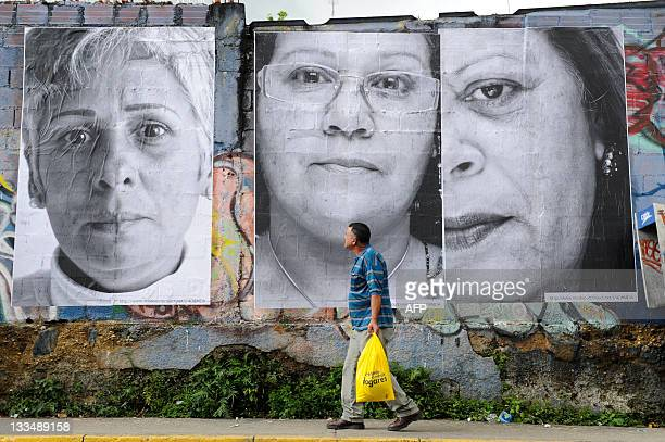 A pedestrians walks in front of giant portraits of women whose children were killed in Caracas on November 19 exhibited to raise people's...
