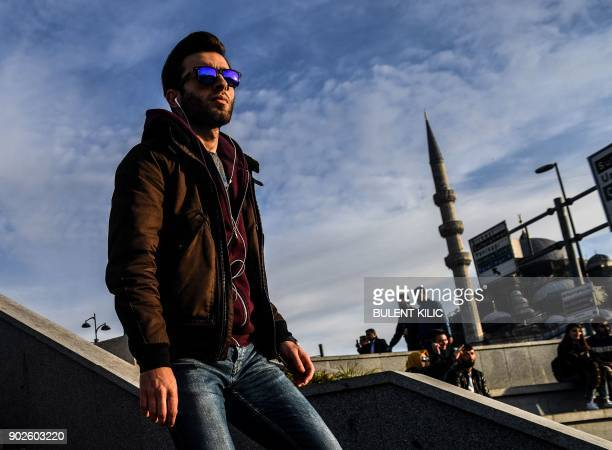 A pedestrians walks in sunshine on a stairway at Eminonu District in Istanbul on January 8 2018 / AFP PHOTO / BULENT KILIC