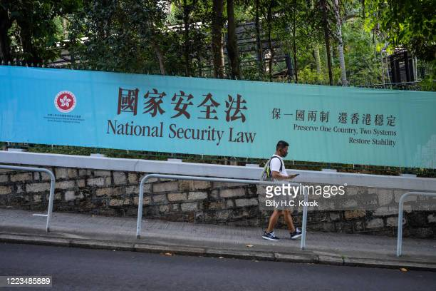 Pedestrians walks past a government-sponsored advertisement promoting a new national security law on June 30, 2020 in Hong Kong, China.