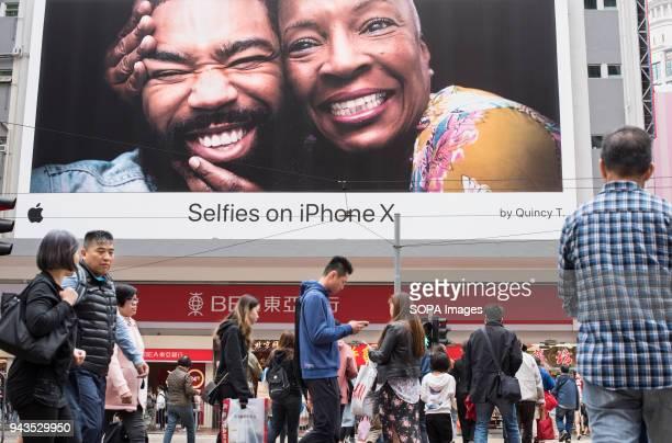 Pedestrians walks past a large Apple Iphone X advertisement in Causeway Bay Hong Kong