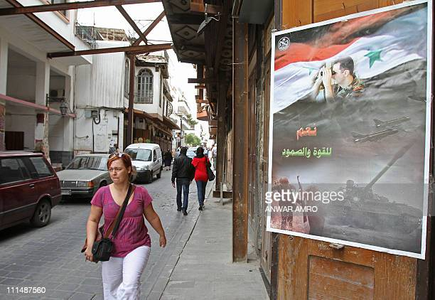 Pedestrians walks past a poster bearing a picture of Syrian President Bashar alAssad superimposed on a national flag with the slogan 'Yes for power...