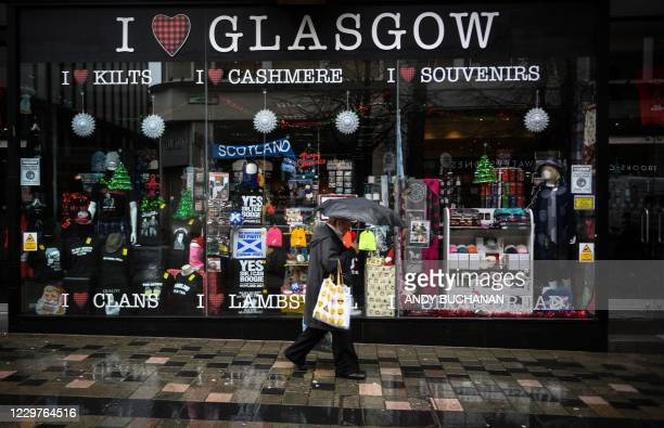 Pedestrians walks past a souvenir shop on Suachiehall Street in central Glasgow, on November 24 during further coronavirus restrictions in the city....