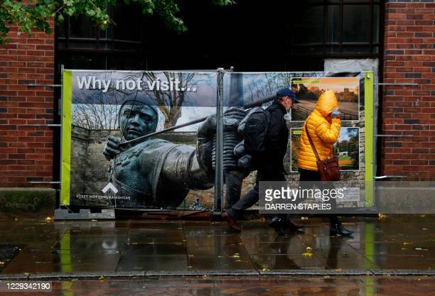 Pedestrians walks past a tourist advert in Nottingham, central England as the city moves into Covid-19 Tier 3 restrictions on October 29, 2020.