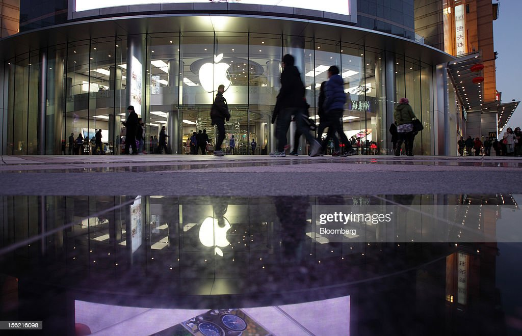 Pedestrians walks past an Apple Inc. store in Beijing, China, on Sunday, Nov. 11, 2012. China's retail sales exceeded forecasts and inflation unexpectedly cooled to the slowest pace in 33 months, signaling the government is boosting growth without driving a rebound in prices. Photographer: Tomohiro Ohsumi/Bloomberg via Getty Images