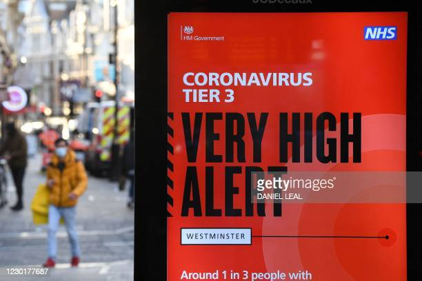 Pedestrians walks past an electronic billboard with a government message displaying the current Coronavirus Tier 3 alert level in central London on...