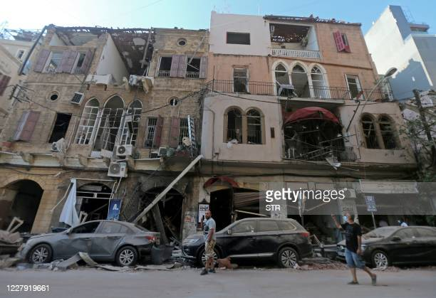 Pedestrians walks past damaged historic buildings on August 5, 2020 in Beirut's Gimmayzeh district which was heavily damaged by the previous day's...