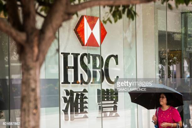 A pedestrians walks past HSBC signage in the Admiralty district of Hong Kong on July 31 2017 HSBC said on July 31 pretax profit for the first half of...