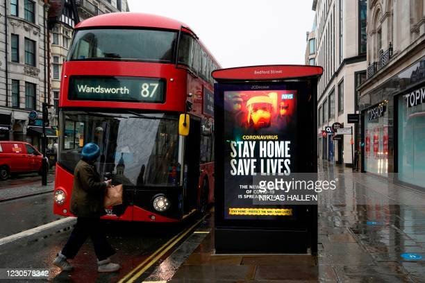 """Pedestrians walks past NHS signage promoting """"Stay Home, Save Lives"""" on a bus shelter in London on January 14, 2021 during Britain's third..."""