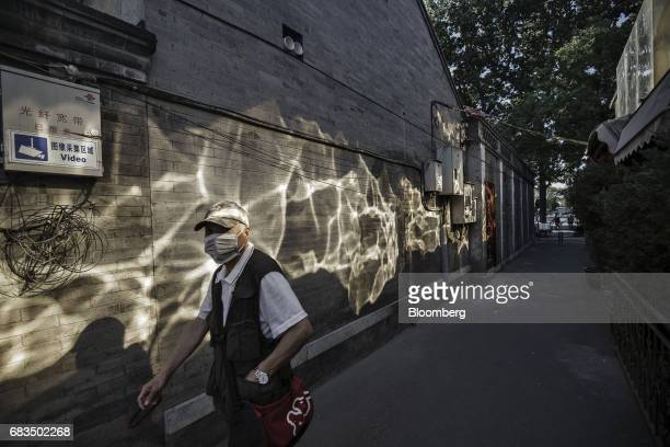 A pedestrians walks past reflections of light falling on a wall in an alleyway in a traditional hutong neighborhood in Beijing China on Sunday May 14...