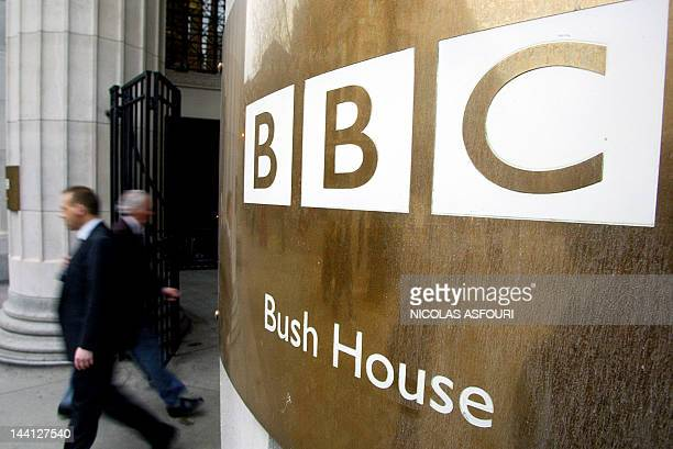 Pedestrians walks past the doors of the BBC's Bush House in London 07 December 2004 The BBC said it would eliminate 2900 jobs or more than 10 percent...