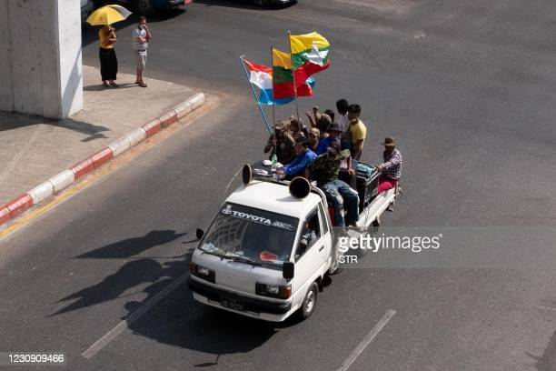 Pedestrians watch as military supporters hold the national and army flags while shouting slogans as they take part in a rally in Yangon on February 1...