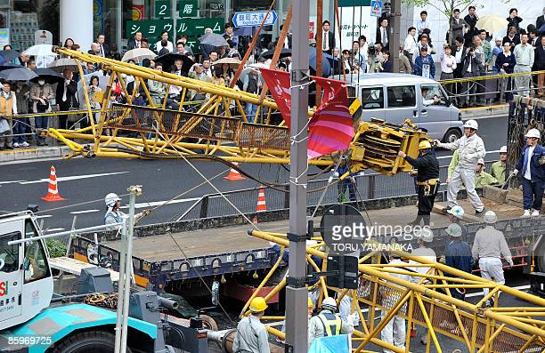 Pedestrians watch as workers remove a section of a pile driver which overturned on the street at a construction site in Tokyo on April 14 2009 The...