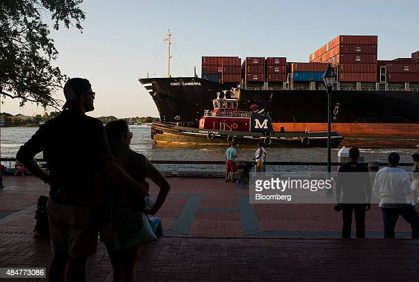 Pedestrians watch from River Street as a cargo ship and a tug boat travel into the Port of Savannah on the Savannah River in Savannah, Georgia, U.S.,...