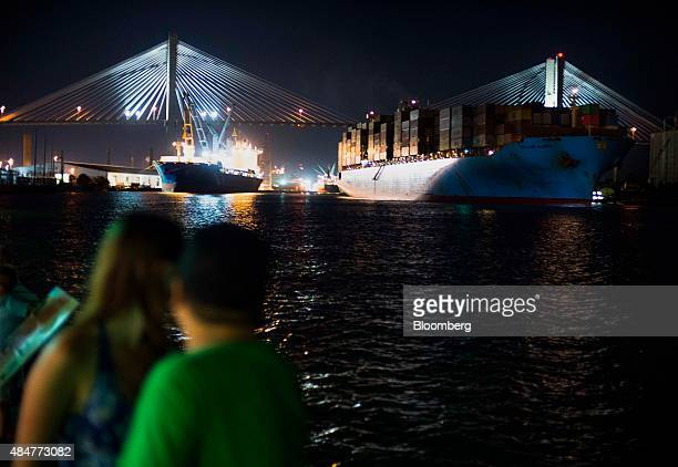 Pedestrians watch from River Street as a cargo ship leaves the Port of Savannah at night on the Savannah River towards the Talmadge Memorial Bridge...