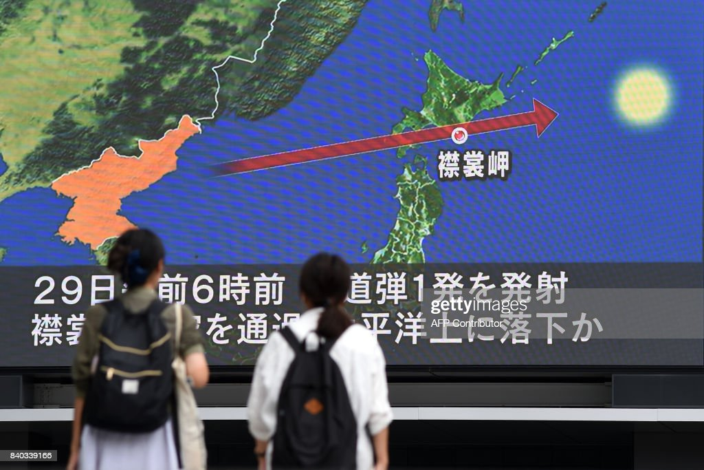 Pedestrians watch the news on a huge screen displaying a map of Japan (R) and the Korean Peninsula, in Tokyo on August 29, 2017, following a North Korean missile test that passed over Japan. Japanese Prime Minister Shinzo Abe said on August 29 that he and US President Donald Trump agreed to hike pressure on North Korea after it launched a ballistic missile over Japan, in Pyongyang's most serious provocation in years. / AFP PHOTO / Toshifumi KITAMURA