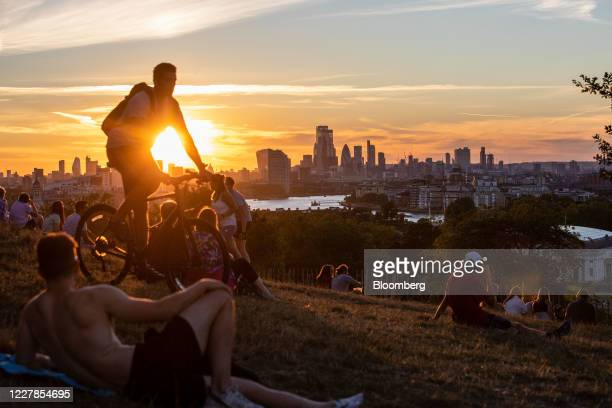 Pedestrians watch the sun set over skyscrapers on the skyline from Greenwich Park in London, U.K., on Thursday, July 30, 2020. London's best offices...