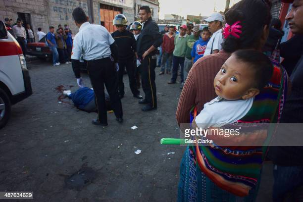 Pedestrians watch volunteer paramedics checking the vitals of a man who was shot in the head while entering his house January 16 2014 in Guatemala...