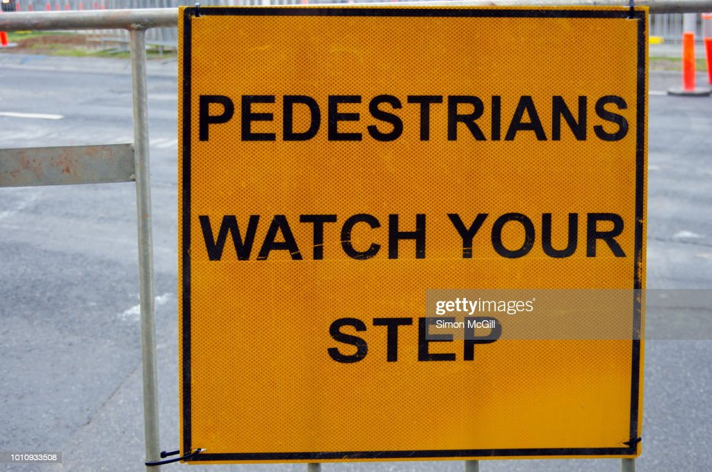 Pedestrians Watch Your Step Sign On Temporary Metal Barricade