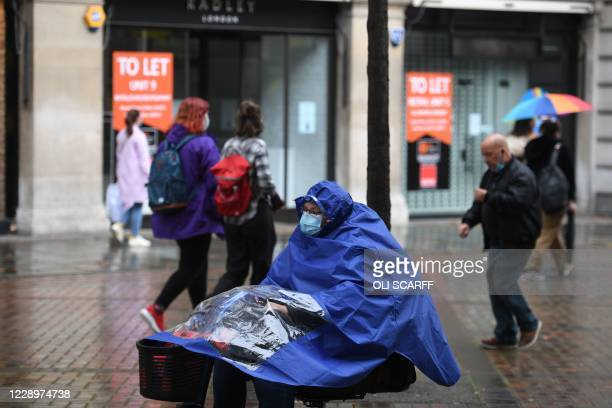Pedestrians wear a protective face coverings in central Nottingham in central England on October 9, 2020. - Pubs and restaurants in coronavirus...