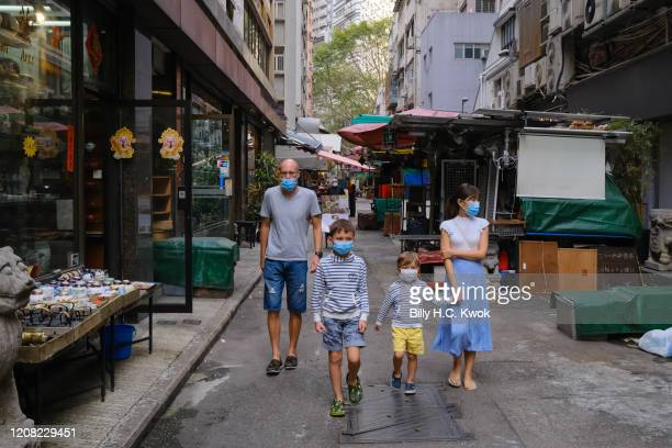 Pedestrians wear face masks as a precaution against the spread of Coronavirus during a coronavirus outbreak on March 26 2020 in Hong Kong China...