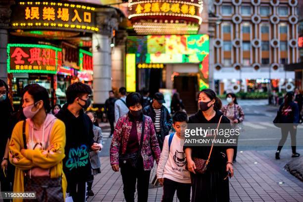 Pedestrians wear face masks as they walk along a pavement in Macau on January 22 after the former Portuguese colony reported its first case of the...