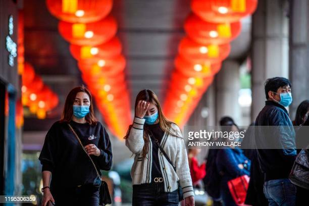 TOPSHOT Pedestrians wear face masks as they walk outside the New Orient Landmark hotel in Macau on January 22 after the former Portuguese colony...