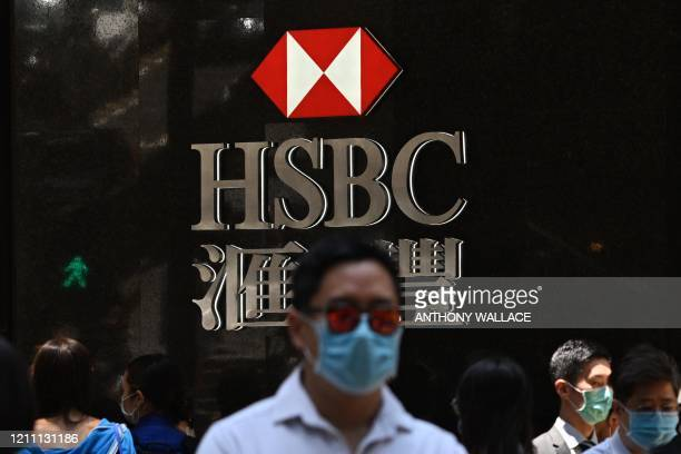 Pedestrians wear face masks as they walk past HSBC signage outside a branch of the bank in Hong Kong on April 28, 2020. - HSBC on April 28 said first...