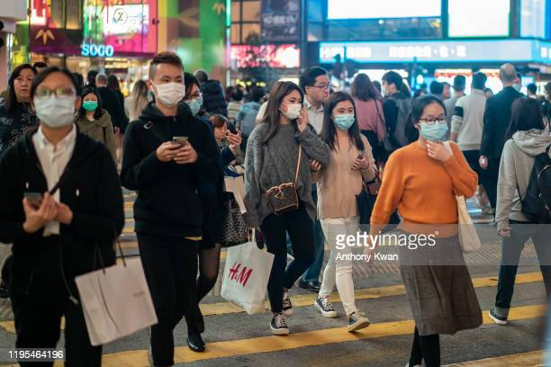 Pedestrians wear face masks as they walk through a crosswalk in Causeway Bay district on January 23 2020 in Hong Kong China Hong Kong reported its...