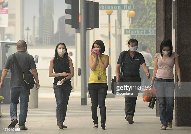 Pedestrians wear face masks as they walk through the central business district of Singapore, on Friday, June 21, 2013. Singapore's smog hit its worst...