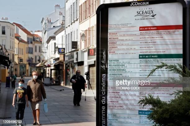 Pedestrians wear face masks in the main street of Sceaux, south of Paris, on April 8 on the 23rd day of a strict lockdown in France aimed at curbing...