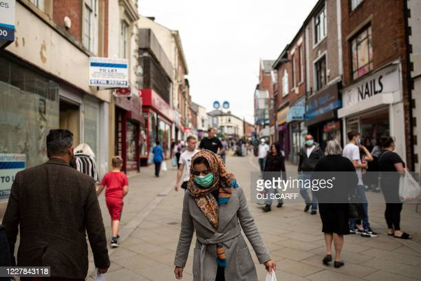 Pedestrians wear facemasks as they walk through a pedestriansed street in Oldham greater Manchester northwest England on July 30 2020