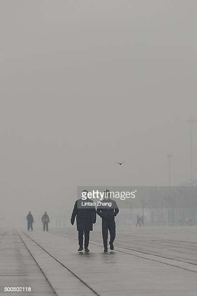 Pedestrians wear masks on a heavy pollution day on December 8 2015 in Beijing China Schools across Beijing have closed and outdoor construction...