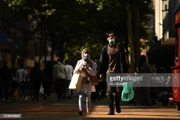 Pedestrians wearing a face mask or covering due to the COVID19 pandemic carry shopping bags as they walks in Birmingham central England on September...
