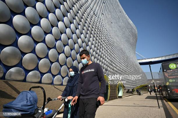 Pedestrians wearing a face mask or covering due to the COVID19 pandemic push a buggy as they walk past the Selfridges building in Birmingham central...