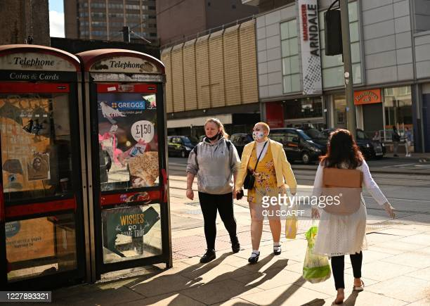 Pedestrians wearing a face mask or covering due to the COVID19 pandemic walk past an advert for food retailer Greggs near the Arndale shopping centre...