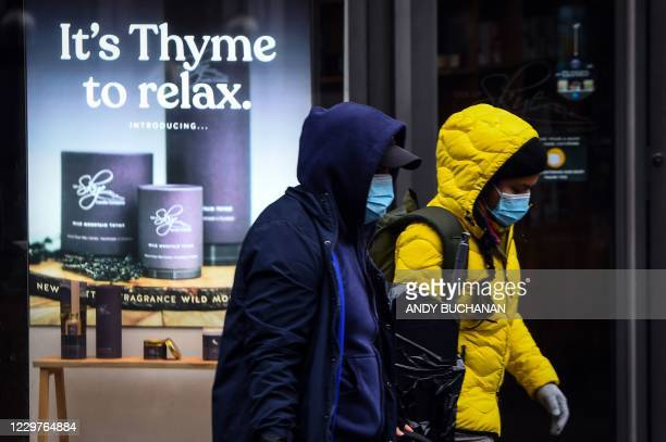 Pedestrians wearing a face mask or covering due to the COVID-19 pandemic, walk on Buchanan Street in central Glasgow, on November 24 during further...