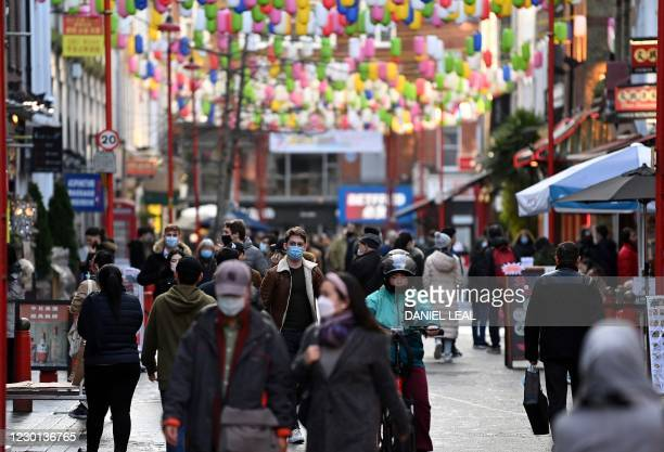 Pedestrians wearing a face mask or covering due to the COVID-19 pandemic, walk along a busy street in London on December 15 as the city prepares to...