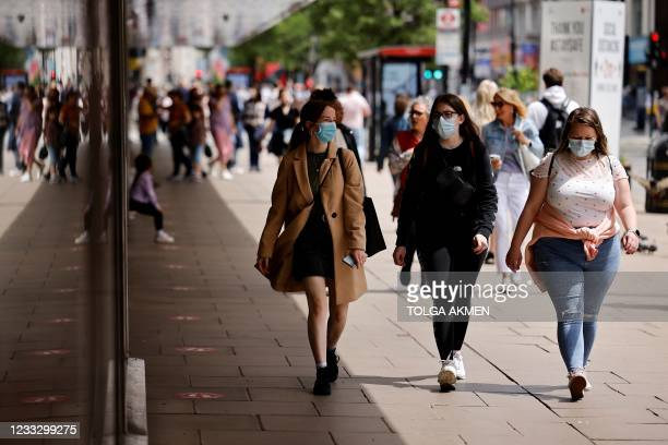 Pedestrians wearing a face mask or covering due to the COVID-19 pandemic, walk along Oxford Street in central London on June 6, 2021. - The Delta...